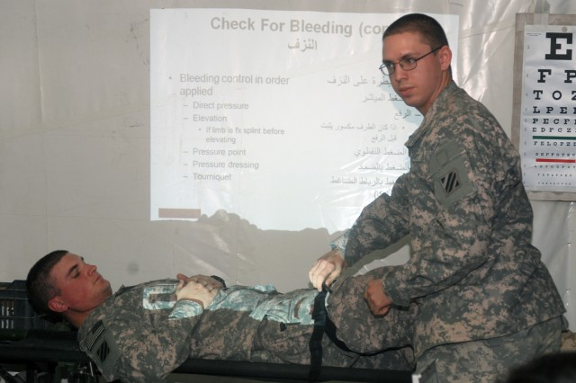 Spc. Johnathan Montgomery, A Troop, 3rd Squadron, 1st Cavalry Regiment, 3rd Heavy Brigade Combat Team, 3rd Infantry Division, demonstrates how to apply a tourniquet to an injured limb with the assistance of Pvt. Alan Murray, who played the casualty, during a first aid class at Contingency Operating Location Shocker, Feb. 25, 2010. The tourniquet is one method to control bleeding that Iraqi border guards, from 3rd Battalion, 7th Brigade, Department of Border Enforcement, learned during the class.