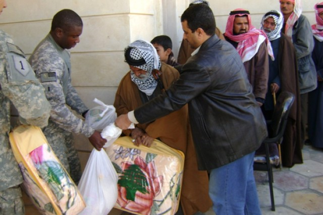 First Lt. Nate Crawford, of Lorton, Va., helps pass out goods to locals in downtown Samawah, Iraq. The event, which gave deprived area families desperately needed supplies for winter, was made possible through the assistance of Company A, 1st Battalion, 77th Armor Regiment, Task Force Pathfinder, and the Muthanna Provincial Reconstruction Team.