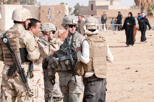 RAMADI, Iraq - 1st Lt. Jesse Burnette, a platoon leader with Company B, 2nd Battalion, 504th Parachute Infantry Regiment, 1st Brigade, 82nd Airborne Division (Advise and Assist), talks to an Iraqi Army commander responsible for outer security at the al-Schmookh School voting center in Ramadi, Iraq, during Election Day March 7. The army and police provided 100 percent of the security at election centers. (U.S. Army photo by Sgt. Michael J. MacLeod, 1/82 AAB, USD-C)