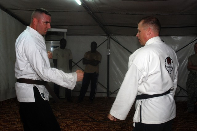 Maj. Rob Boone, right, instructs Staff Sgt. William Morris on proper stance during a karate class at Contingency Operating Location Shocker, Feb. 23, 2010. Boone, who has been involved in karate for over 12 years, uses the class to help relieve stress and pass on self defense skills to Soldiers, Iraqis and the Ugandan guards employed by Saber International to protect the COL.
