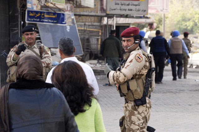 BAGHDAD - Iraqi Army soldiers direct civilians to a voting site in Mansour March 7 during Iraq's historic national elections. Before passing through to the polling site, voters were searched thoroughly.