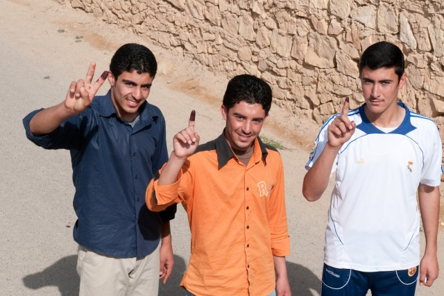 Three young men of Ramadi, Iraq, smile while showing their dyed purple fingers after voting in national parliamentary elections March 7. The three had just voted at the al-Schmookh School voting center.