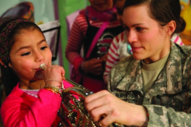 Sgt. Emily Burgess, a member of the Cantigny Brass Quintet who hails from Jewell, Kan., shares her instrument with a girl who attended the Wasit Arts Cultural Festival Feb. 27, 2010. The quintet, part of the 1st Infantry Division band, performed for almost five hours during the event.