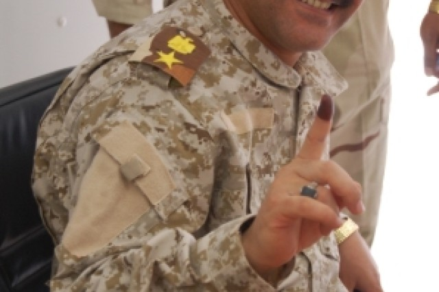 Lt. Col. Nabras, 8th Iraqi Army Division, proudly displays his purple finger, March 5, 2010, at the Mid-Euphrates Operations Center at Contingency Operating Station Echo, Iraq, indicating he voted during the special needs elections, March 4.