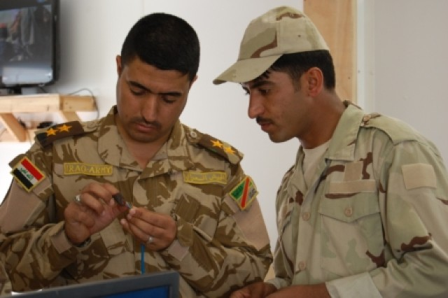 Two Soldiers from the 8th Iraqi Army Division work to connect computer cables at the Mid-Euphrates Operations Center, March 5, 2010, at Contingency Operating Station Echo, Iraq.