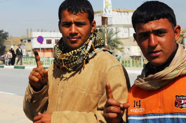 Two Iraqi men near a Karbala, Iraq, polling site after one has cast his vote during the Iraqi national elections, March 7, 2010. Iraqi citizens of various ages were seen leaving polling sites with the painted finger - a mark of voting.