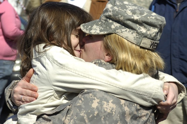 GREENSBURG, Pa. - 1st Lt. Sarah Weber kisses her daughter after returning from a year-long deployment in Iraq at the U.S. Army Reserve Center here Sunday. Weber served as the acting commander for the 14th Quartermaster Company during the deployment, responsible for her platoon and two others. (US Army Photo by Spc. Michael T. Crawford, 316th ESC Public Affairs Office)