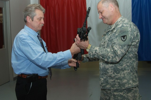 Col. Craig S. Cotter, commander Rock Island Arsenal, receives a M14 EBR rifle from Doug Carlstrom, an equipment specialist from TACOM Rock Island.