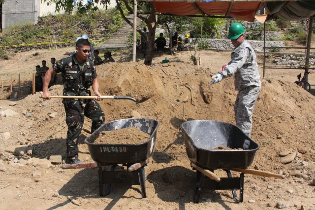 An Armed Forces of the Philippines and U.S. Army soldiers fill wheelbarrows with backfill dirt that will be used to set footings for a new schoolhouse structure February 16, 2010 at the Pias Elementary School in Salcedo, Ilocos Province, Philippines.  The schoolhouse build is one of several Engineer Civil Action Projects (ENCAP) taking place during Balikatan 2010.   Balikatan 2010 is a bilateral exercise and security assistance program between the U.S. military and the Armed Forces of the Philippines.  The exercise ensures disaster relief efforts are more responsive, efficient and effective and complement U.S. and Philippine reconstruction efforts done in the wake of the typhoons that devastated parts of the Philippines in 2009.