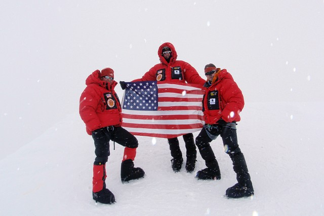 Retired Sgt. 1st Class Bob Haines (holding the flag), Lt. Col. Marc Hoffmeister (right) and Spc. David Shebib pose for a picture after Shebib's re-enlistment at the summit of Alaska's Mount McKinley, June 16, 2009.