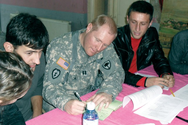 Capt. Jeff M. Couch, of the 2-151st Aviation Battalion of South Carolina, works with high school students in an English as a Second Language Class at the Ferizaj, Kosovo, Youth Center.