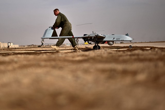 CAMP TAJI, Iraq - After a Shadow unmanned aerial vehicle makes its landing, Spc. Ben Hughes, from Fort Drum, N.Y., a Shadow UAV maintainer in 2nd Brigade Special Troops Battalion, 2nd Brigade Combat Team, 10th Mountain Division, U.S. Division-Center, pushes the aircraft off of the flight line to the maintenance bay March 7. The maintainers, attached to Company G, 2nd Battalion, 227th Aviation Regiment, 1st Air Cavalry Brigade, 1st Cavalry Division, conduct inspections of the aircraft after each flight as part of the diligence needed to sustain operations and reach 20,000 flight hours in a 10-month period.