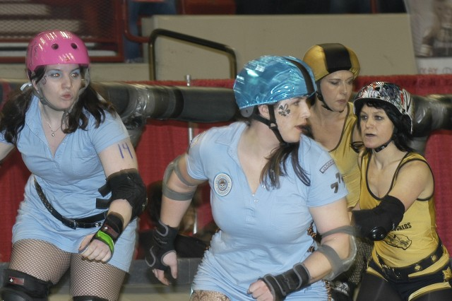 1st Lt. Jessica duMonceaux, center, and Sgt. Karli Wahkahquah, left, look to score a point during a roller derby bout against the Los Angeles Derby Dolls. Both are member of the Oklahoma Army National Guard's 45th Infantry Brigade Combat Team.