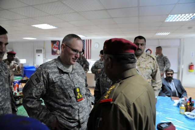 During a dinner at Contingency Operating Station Endeavor, Iraq, a small outpost outside of Najaf, Brig. Gen. Ricky Gibbs (left), the United States Division-South deputy commanding general for maneuver, speaks with Col. Murad, a brigade commander in the 30th Iraqi Army Division (right), Feb. 24, 2010. The informal dinner, held to celebrate President's Day, allowed Iraqi and U.S. military leaders, diplomats, politicians, influential businessmen and shaykhs to sit down and get to know one another on a more personal level.