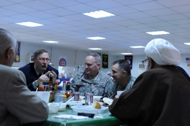 Following a dinner at Contingency Operating Station Endeavor, Iraq, a small outpost outside of Najaf, Brig. Gen. Ricky Gibbs (second from the left), deputy commanding general for maneuver, United States Division-South, listens as Angus Simmons, the team leader for the Najaf Provincial Reconstruction Team (left), speaks with local leaders from the province, Feb. 24, 2010. The informal dinner, held to celebrate President's Day, allowed leaders like Simmons and Gibbs to sit down and listen to the goals of their Iraqi counterparts in an informal setting.