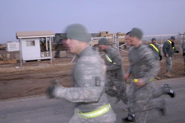 The competitors take off from the start line during the run portion of the Army Physical Fitness Test event near the flight line during the Task Force 12 Best Warrior Soldier and Noncommissioned Officer Competition at Contingency Operating Base Adder, Iraq.""