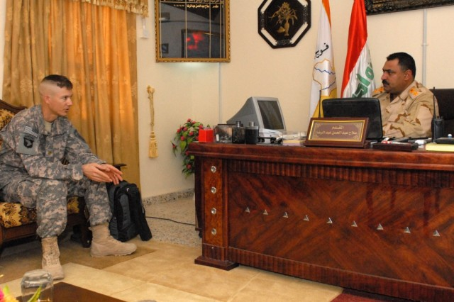 Maj. Stefan Lockton, team chief for the 30th Military Transition Team, speaks with Lt. Col. Salah, commander of the 3rd Battalion, 30th Iraqi Army Division, during a meeting at the 3rd Bn.'s headquarters in Najaf Province, Iraq, Feb. 23, 2010. Lockton, who has worked with 30th IA Div. since June, helps schedule training with Iraqi Security Force leaders to ensure the ISF can operate more efficiently.