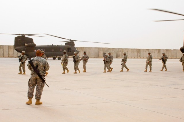 """Soldiers set foot on Contingency Operating Station Hunter, Iraq, after exiting CH-47 Chinooks from the 1st Infantry Division's """"Big Red Express,"""" Feb. 24, 2010, before receiving directions to the passenger marshalling area from Staff Sgt. Armando Ortiz, Headquarters and Headquarters Troop, 2nd Squadron, 13th Cavalry Regiment, a human resources specialist from Ponce, Puerto Rico."""