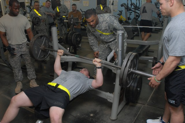 """The judge and organizer of the March 1, 2010, Gunslinger Strongman Competition at Contingency Operating Base Basra, Iraq, 1st Sgt. Derrick Bazile, 1st Battalion """"Gunslingers,"""" 377th Field Artillery Regiment, watches to see if Pfc. Matthew A. Moses fully extends on this 225-pound bench press. The Gunslingers, an element of the 17th Fires Brigade, are the only air assault battalion in its branch."""