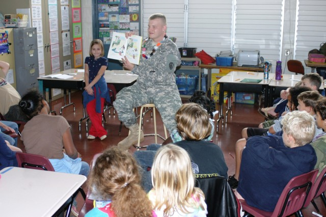 """Pfc. Joseph Foster, Company A, 25th Infantry Division Special Troops Battalion, reads a """"Curious George"""" book to the kids during """"Tell Me a Story"""" event at the Wheeler Elementary School, Wheeler Army Air Base, Hawaii, Mar. 04. (U.S. Army photo by Spc. Mahlet Tesfaye, 25th Infantry Division Public Affairs Office)"""