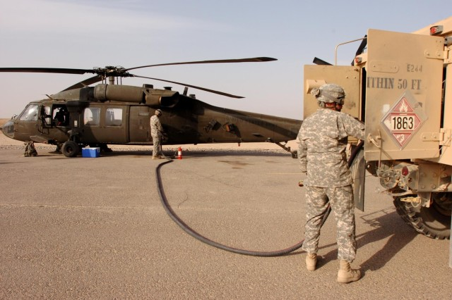 """Soldiers of Company E, """"Road Runners,"""" 2nd Battalion, 25th Aviation Regiment, Task Force Diamond Head, re-fuel a UH-60 Black Hawk helicopter at Contingency Operating Base Speicher, near Tikrit, Iraq, Feb.5. Cold re-fuel and de-fuel operations are conducted after an aircraft is shutdown. (Photo by: Staff Sgt. Mike Alberts  25th Combat Aviation Brigade Public Affairs)"""