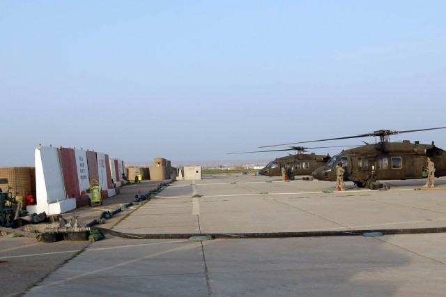 Two UH-60L Black Hawk helicopters are re-fueled by Soldiers from Troop E, 2nd Squadron, 6th Cavalry Regiment, Task Force Lightning Horse, at the Lightning Horse Forward Arming and Re-fueling Point, at Contingency Operating Site Warrior, near Kirkuk, Iraq, Feb. 14. (Photo by:  Sgt. 1st Class Tyrone C. Marshall  25th Combat Aviation Brigade Public Affairs).