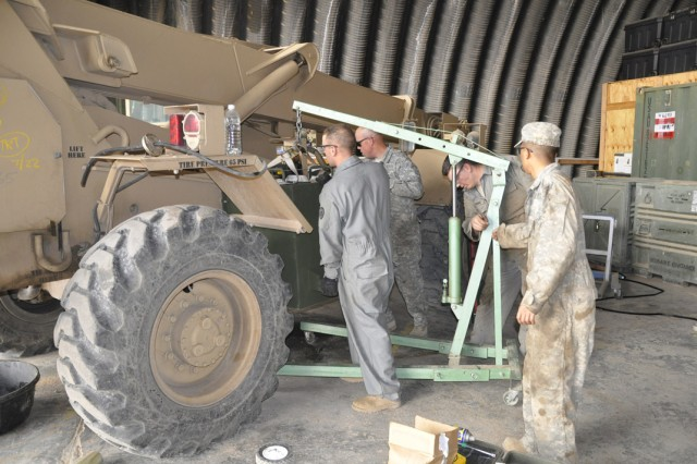 Maintenance Soldiers from Troop E, 2nd Squadron, 6th Cavalry Regiment, Task Force Lightning Horse, load a fuel tank onto a crane as they prepare to move it from their motor pool for installation, at Contingency Operating Site Warrior, near Kirkuk, Iraq, Feb. 17. (Photo courtesy of U.S. Army).