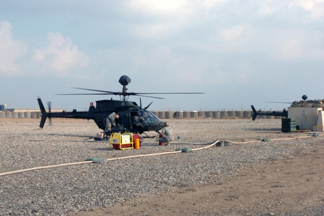 Troopers from 2nd Squadron, 6th Cavalry Regiment, Task Force Lightning Horse, re-fuel an OH-58D Kiowa Warrior at the Forward Arming and Re-fuel Point at Contingency Operating Location McHenry, in Kirkuk Province, Iraq, Nov. 22, 2009. (Photo by Sgt. 1st Class Tyrone C. Marshall  25th Combat Aviation Brigade Public Affairs)