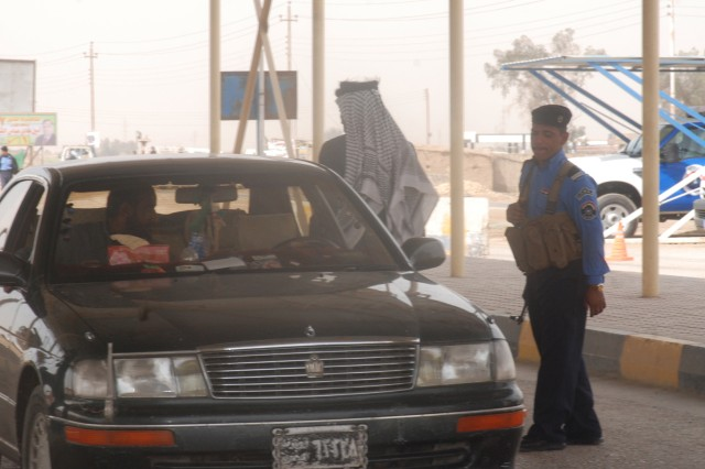 An Iraqi police officer inspects a vehicle as the driver opens the trunk at an Iraqi Police checkpoint on election day, March 7. The Iraqi Police were the primary security for the elections, a major change from the 2005 national elections, when coalition forces provided the primary security for polling sites and cities.