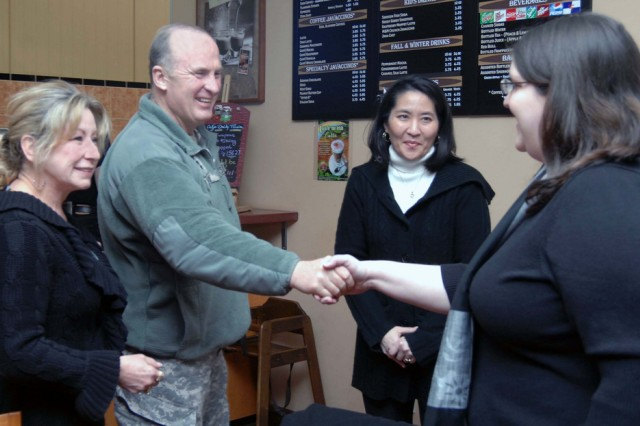 Lt. Gen. Rick Lynch, commander of Installation Management Command, and his wife, Sarah, greet Army spouse Sara Arnett as fellow spouse Lawna Crossfield looks on during the general's first visit to U.S. Army Garrison Kaiserslautern March 9 at the garrison's Java Café on Rhine Ordnance Barracks.