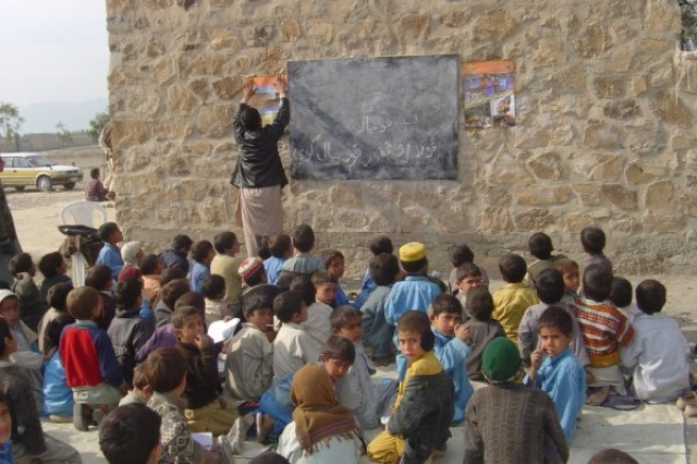 Afghan children attend school in an outdoor classroom.