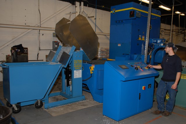 Logan Tuttle, machinist helper, and Christopher Shaffer, machine tool operator, empty aluminum chips into a recycling cart.  The carts, filled with chips generated in the machine shop, are then dumped into a hopper and fed through the metal compactor producing bars of compressed aluminum for recycling.