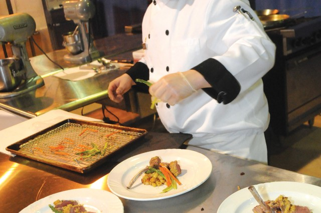Pfc. Michael Cutright, Joint Base Langley- Eustis, adds vegetables to his dish during the Practical and Contemporary Hot Food Cooking, Professional, category of the 35th Army Culinary Arts Competition. Contestants put in months of practice for the opportunity to present their best work to judges.