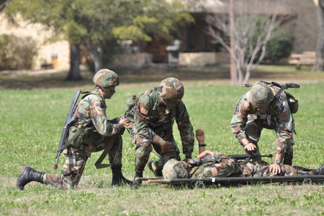 Soldiers demonstrate how combat medics of the past would treat and evacuate a wounded Soldier on the battlefield during a ceremony held March 9 at Fort Sam Houston.