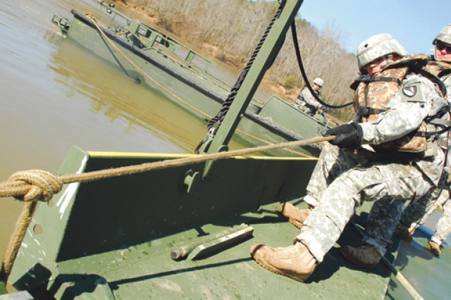 Soldiers with a bay squad pull a bridge section into the correct position.