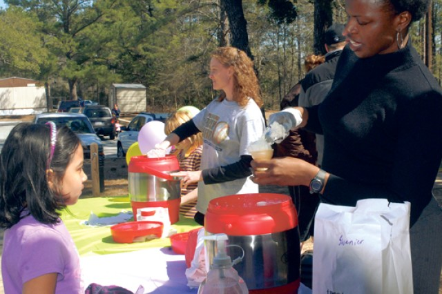 Volunteers Kaisha Nesmith and Shelley Calhoun scoop chocolate and vanilla ice cream for children of deployed Soldiers.  The event was hosted by WNBA player and Columbus High School graduate Ketia Swanier.