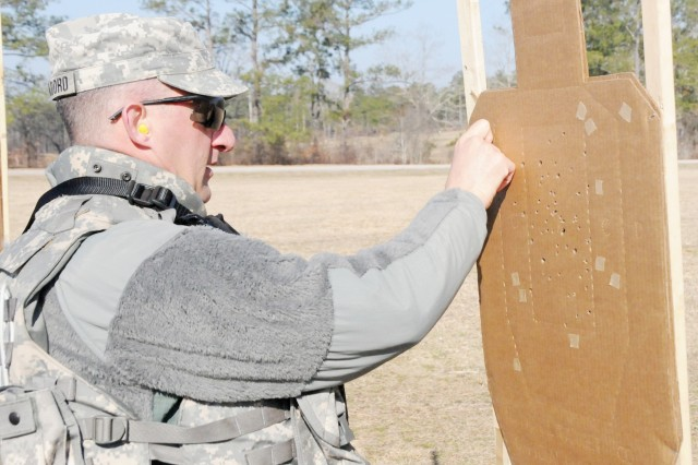 CW4 John Cappadoro, ASDAT, marks wide shots with tape after target practice with the Army Marksmanship Unit March 5.