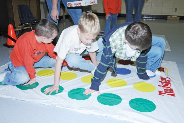Fort Rucker Primary School students try their hands and feet at Twister March 4 during Dr. Seuss Week. From left are Austin Henry, 6; Gavin Mann, 7; and Bryan Roderick, 7.