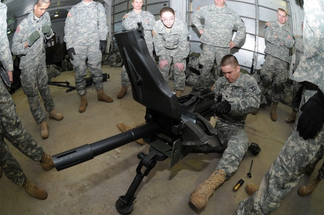Spc. Andrew Finch performs a functions check on an M-19 grenade machine gun, using inert training rounds, during a pre-marksmanship training session in a Fort McCoy, Wis., classroom. Finch is with the 379th Engineer Company, a Massachusetts Army National Guard unit training to deploy in support of Operation Enduring Freedom.