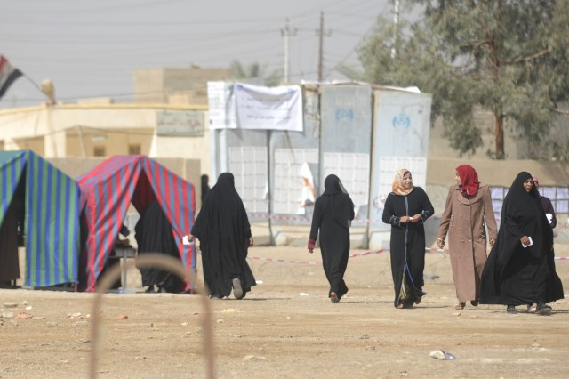 Iraqi women leave a polling site in Baghdad after voting during the parliamentary elections, March 7, despite multiple improvised explosive device attacks throughout the morning. Iraqi federal and local forces patrolled the area throughout the day to keep insurgent attempts from reaching polling sites.