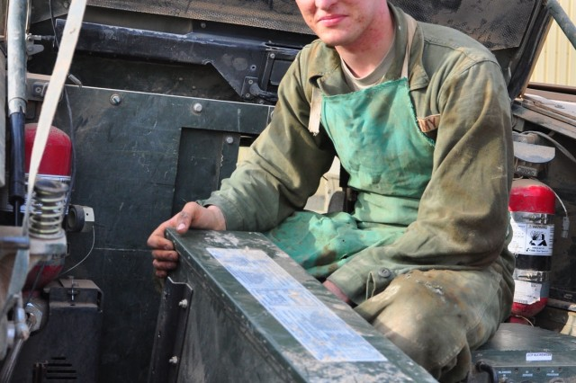 Private First Class Andrew Lamar, Forward Support Company, 1/64 Armor, 2md HBCT, 3rd ID, shows off the bracket that he and fellow Soldier Pfc. Chad Loskota fabricated that the U.S. Army is interested in implementing throughout the Army.