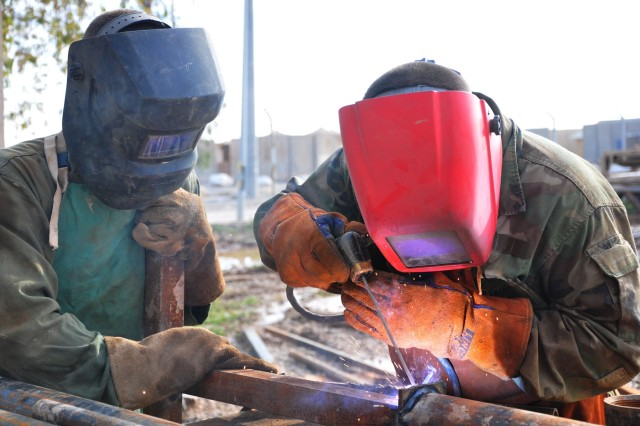 Private First Class Andrew Lamar and Pfc. Chad Loskota, Forward Support Company, 1/64 Armor, both Bradley Fighting Vehicle mechanics fill the role of welders for the Desert Rogue battalion.