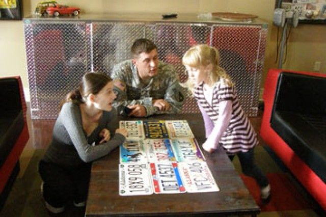 From left to right: Anuschka Munger, Sgt. Thomas Munger and Kimberly Munger, 5, check out the coffee table in the club room. The Mungers cut the ribbon at the grand opening of the Dogwood Terrace Neighborhood Center March 9. The theme of American cars and related memorabilia can be seen throughout the room.