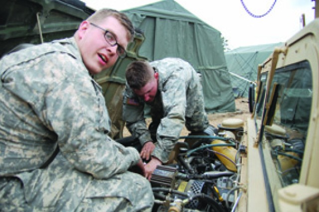 Spc. Sean Melchert (left) and Spc. Daniel House performs maintenance on a vehicle belonging to the 88th BSB, 1st MEB, during a field exercise at Peason Ridge March 8.