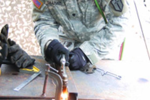 Spc. Alfred Graham, B Company, 88th Brigade Support Battalion, 1st Maneuver Enhancement Brigide, cuts a piece of metal with a torch during a field exercise March 8 at Fort Polk's Peason Ridge Training Area.