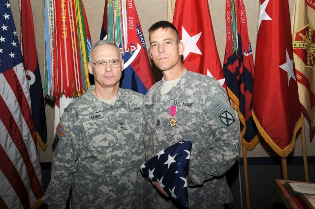 Maj. Gen. James L. Terry, 10th Mountain Division (LI) and Fort Drum commander, congratulates outgoing Division Command Sgt. Maj. James W. Redmore during his retirement.