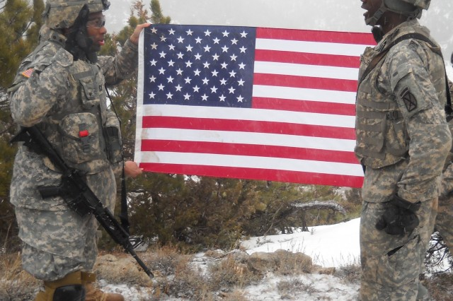 CAMP GUERNSEY, Wyo. - Pvt. Timothy English (right), Company F, 2nd Battalion, 30th Infantry Regiment, re-enlists atop a mountain during off-post training at Camp Guernsey, Wyo. as his company commander, Capt. Derrick Lyles, read the oath of enlistment, Feb. 13.