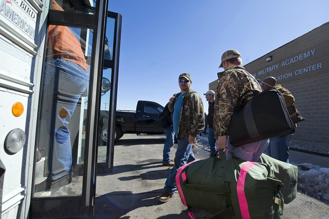 Mechanics from several U.S. Army depots across the nation load onto a bus to deploy to Iraq after undergoing a civilian mobilization course at the Camp Atterbury Joint Maneuver Training Center in central Indiana.