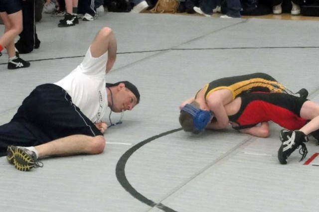 COLORADO SPRINGS, Colo. - Pfc. Brad Bellas, Headquarters and Headquarters Company, 2nd Special Troops Battalion, 2nd Brigade Combat Team, 4th Infantry Division, referees a wrestling match in the Dan Gable Pee-Wee/Junior wrestling tournament Jan. 30. Bellas and other Soldiers from his company volunteer their time for youth wrestlers in the area.