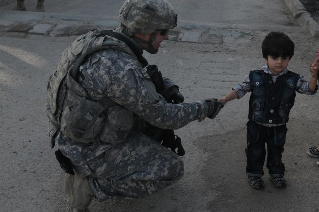 Pfc. Alexander J. Miller, an armored infantry cavalry scout with A Troop, 1st Squadron, 82nd Cavalry Regiment, 41st Infantry Brigade Combat Team, 13th Sustainment Command (Expeditionary) and a Canby, Ore., native, talks to an Iraqi child while his family member goes through the screening process March 8, at entry control point 13 at Victory Base Complex, Iraq.